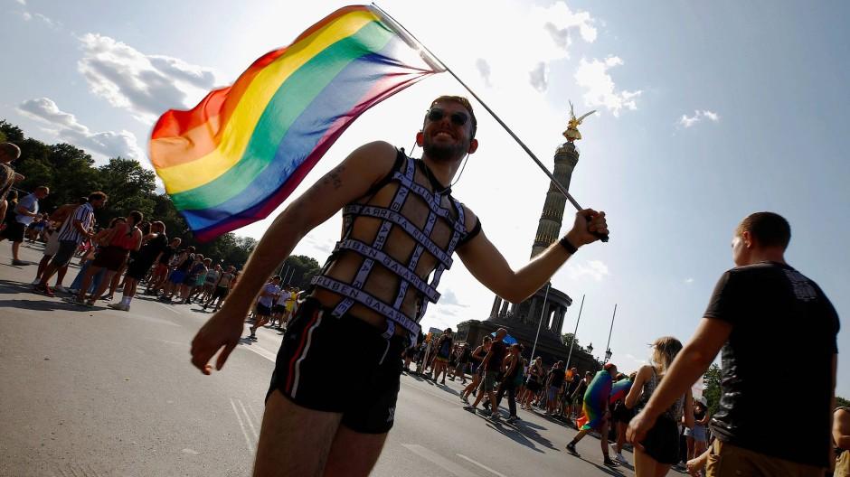 Junger Mann feiert vor der Siegessäule am CSD in Berlin