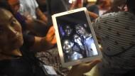 Ein Hoffnungsschimmer: Angehörige der verschollenen Fußballjungen halten ein Foto in den Händen, das vier der 13 Vermissten zeigt. Kurz zuvor hatten sie Nachricht erhalten, dass die Jungen gefunden worden waren.