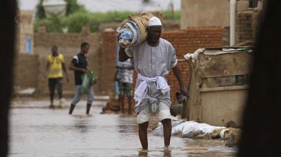 Die Habseligkeiten auf der Schulter wandert ein Mann am 31. August durch die überfluteten Straßen in Shaqilab, einem Dorf in der Nähe der sudanesischen Hauptstadt Khartum.