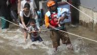 Ein Mitglied der Rettungskräfte trägt ein Baby durch ein überschwemmtes Viertel der indonesischen Stadt Tangerang nahe Jakarta.