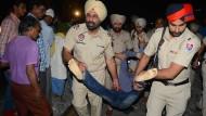 Die Polizei des Bundesstaates Punjab in Indien trägt einen Toten weg vom Unglücksort.