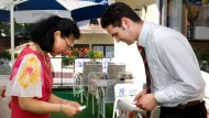 Asiatische Umgangsformen: Die niedriger gestellte Person verbeugt sich tiefer, Visitenkarten nimmt man mit beiden Händen entgegen.