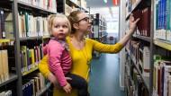 Maria Wappler in der Bibliothek am Campus Westend der Frankfurter Goethe-Universität. Mit dabei: Frida, ihre Tochter.