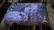Zwei Männer stellen ein Plakat in der von Regierungstruppen belagerten syrischen Stadt Douma auf