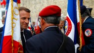 Präsident Emmanuel Macron begrüßt einen Veteranen.