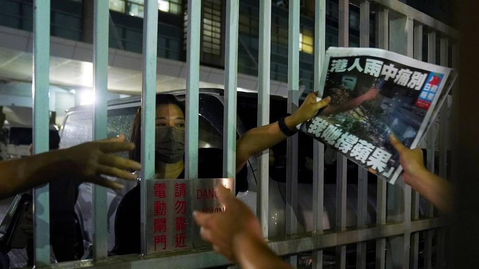"""Die letzte Ausgabe des """"Apple Daily"""" wird am Donnerstag durch ein Tor an einen Unterstützer in Hongkong gereicht."""