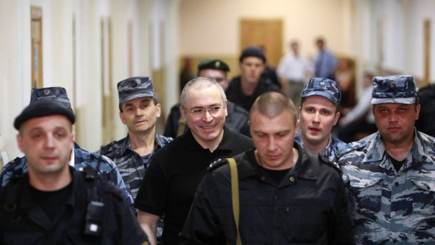 Jailed Russian businessman Mikhail Khodorkovsky is escorted to court in Moscow