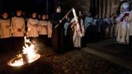 Gedenken an die Auferstehung Jesu Christi von den Toten: Ein Priester zündet in der Osternacht vor dem Münster in Freiburg die Osterkerze an.