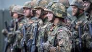 Eine deutsche Bundeswehr-Soldatin steht mit ihren Kameraden bei dem von der Bundeswehr angeführten Nato-Bataillon auf dem Militärstützpunkt in Rukla.
