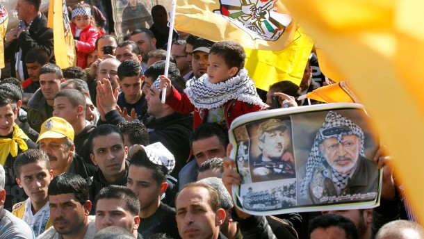 Palestinians Fatah supporters take part in a rally in the West Bank city of Nablus marking the 48th anniversary of the founding of the Fatah movement