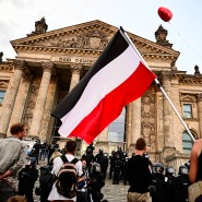 Teilnehmer einer Kundgebung gegen die Corona-Maßnahmen stehen am 28. August vor dem Reichstag, ein Teilnehmer hält eine Reichsflagge.