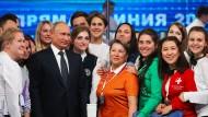 """Russlands Präsident Wladimir Putin posiert zusammen mit Freiwilligen nach der Sendung """"Der direkte Draht"""" am 7. Juni im Moskauer Gostiny Dvor Studio."""