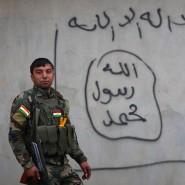Ein kurdischer Peschmerga-Kämpfer vor einer mit IS-Graffiti bemalten Hauswand in Zummar im Nord-Irak. In den vergangenen Tagen hatten kurdische Truppen die Terrormiliz IS zurückdrängen können.