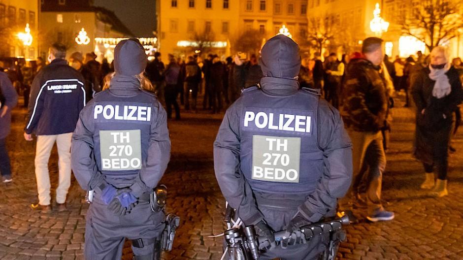 Zwei Polizisten verfolgen die unerlaubte Versammlung gegen die Corona-Proteste am Mittwochabend in Hildburghausen.