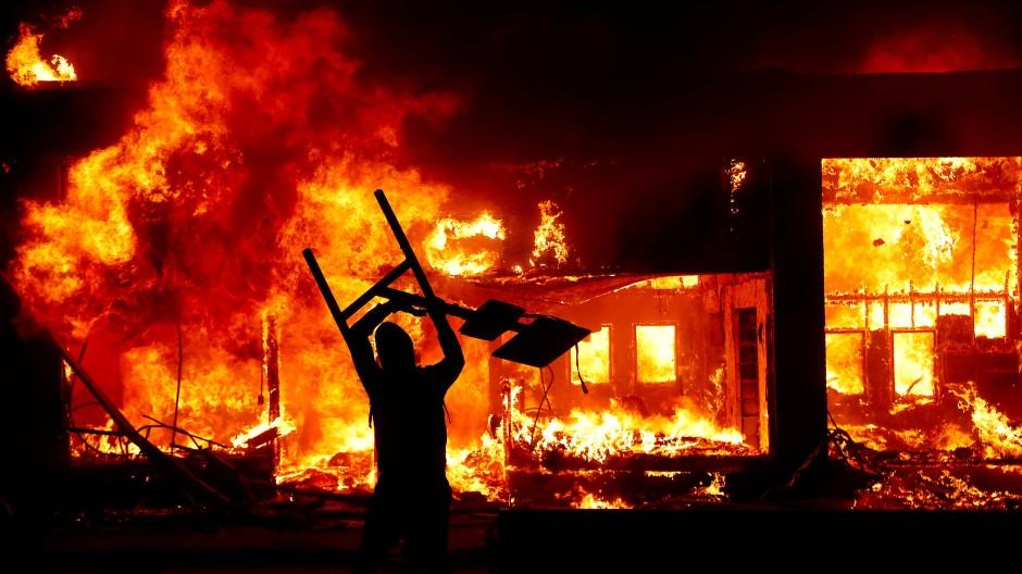 Ein triumphierender Demonstrant vor einem brennenden Haus in Minneapolis in der Nacht auf Samstag