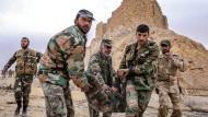 Syrische Soldaten schleppen am Karsamstag einen verwundeten Kameraden aus den Ruinen von Palmyra.