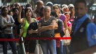 Venezolaner warten hinter einer Absperrung darauf, auf einem Markt Essen einkaufen zu dürfen. Unter anderem wegen der schlechten Versorgungslage könnte nach 17 Jahren erstmals die Opposition gewinnen.