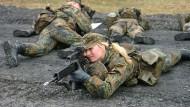 An der Waffe: Eine Rekrutin sichert in Ahlen auf dem Truppenübungsplatz eine Patrouille
