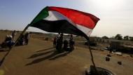 Die sudanesische Fahne an der Grenze zum Südsudan, die nun wieder offiziell geöffnet ist. Im April 2014 prüfen sudanesische Soldaten das Gepäck von Flüchtlingen.