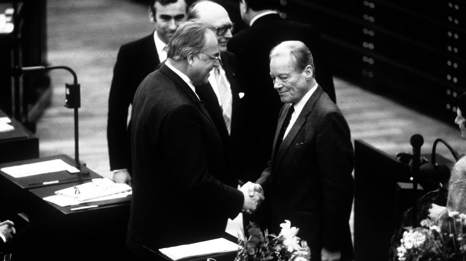 Vom Wähler 1983 bestätigt: Willy Brandt gratuliert Helmut Kohl im Bundestag in Bonn zur Kanzlerwahl.