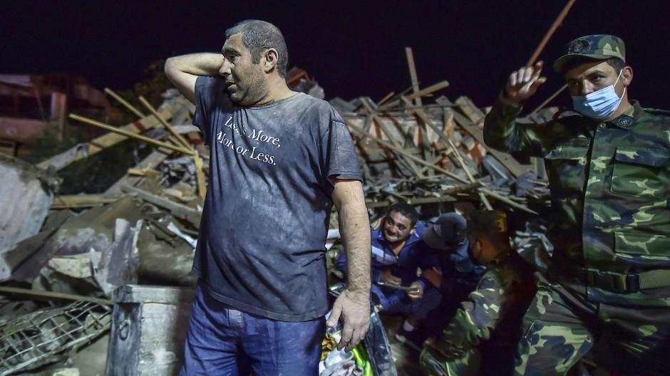 Ein Anwohner und ein aserbaidschanischer Soldat in Gandscha, während Überlebende aus zerstörten Häusern in einem Wohngebiet geborgen werden.