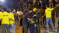 Sexuelle Übergriffe während einer öffentlichen Silvesterfeier im indischen Bangalore: Ein Mann hilft einer Frau hinter die Polizeiabsperrung.