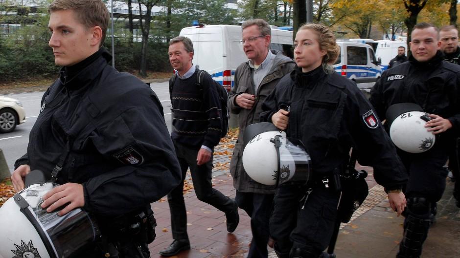 Unter Polizeibegleitung verlässt Bernd Lucke (mit Rucksack) die Uni Hamburg.