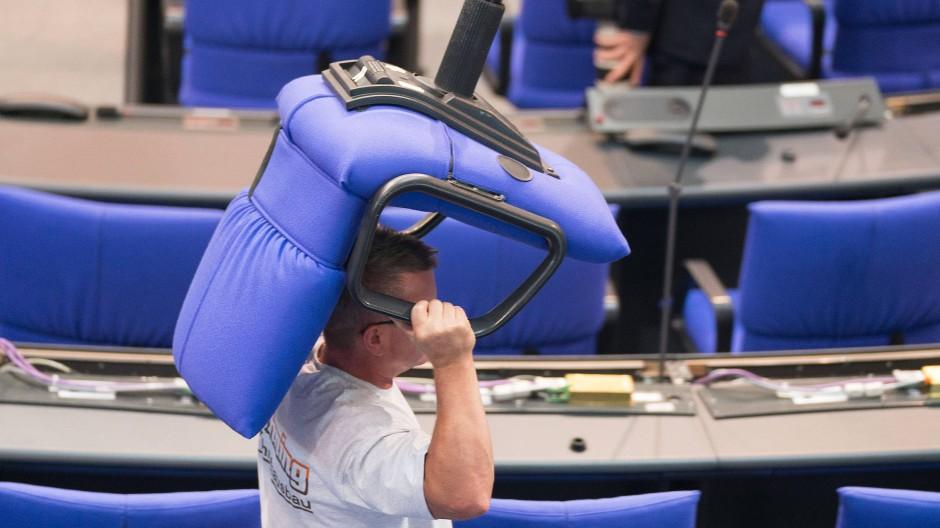 Ein Arbeiter trägt einen Abgeordnetenstuhl durch den Plenarsaal.