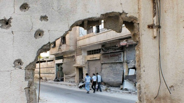Men walking along a road are seen through a hole in a wall in the besieged area of Homs