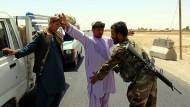 Ein afghanischer Soldat kontrolliert nach dem Anschlag nahe der Militärbasis im Distrikt Kandahar Zivilisten an einem Checkpoint.