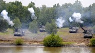 Ein Zug Panzerhaubitzen 2000 der Bundeswehr feuert bei einer Fahrt auf dem Truppenübungsplatz in Munster.