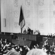 Frei gewählt: Alterspräsident Paul Löbe (M), spricht während der konstituierenden Sitzung des Deutschen Bundestages am 7. September 1949 in der einstigen Turnhalle der Pädagogischen Akademie, die zuvor zum Plenarsaal umgebaut worden war.
