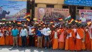 An der Fahrtstrecke der Kolonne des Bundespräsidenten in Varanasi stehen zahlreiche Menschen und winken mit deutschen und indischen Fähnchen.