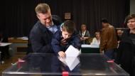 Adrian Zandberg, Chef der linken Partei Lewica Razem, und sein Sohn stimmen am Sonntag in einem Wahllokal in Warschau ab.