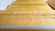 """Im Kühlraum des Krematoriums Dresden-Tolkewitz: Mit Kreide geschrieben steht """"Covid-19"""" auf Särgen mit Verstorbenen, die an oder mit dem Coronavirus gestorben sind."""