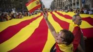 Eine Frau winkt in Barcelona (Spanien) während des Spanischen Nationalfeiertags mit einer spanischen Flagge. Hinter ihr tragen Menschen eine riesige Flagge Kataloniens.