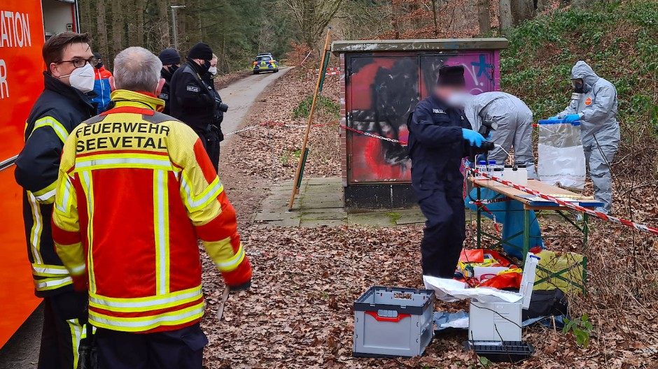 Polizisten untersuchen in einem Waldstück in Seevetal die in dem Erddepot sichergestellten Gegenstände.