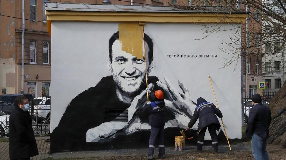 Städtische Arbeiter überstreichen am 28. April in Sankt Petersburg ein Wandgemälde, das den inhaftierten Oppositionspolitiker Alexej Nawalnyj zeigt.