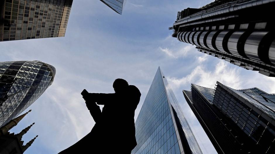 Ein Mann schaut in der City of London auf sein Mobiltelefon (Archivbild).