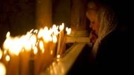 Eine Christin betet am Ostersamstag in der Grabeskirche, die von vielen als Ort der Kreuzigung Jesu angesehen wird. Auch mit dem Judentum und dem Islam gibt es am Osterfest Zusammenhänge und Parallelen.