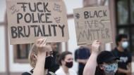 """""""Fuck police brutality"""" steht auf dem Plakat einer Frau, die sich im Mai 2020 in Frankfurt am Main an einer Kundgebung gegen Polizeigewalt beteiligt."""