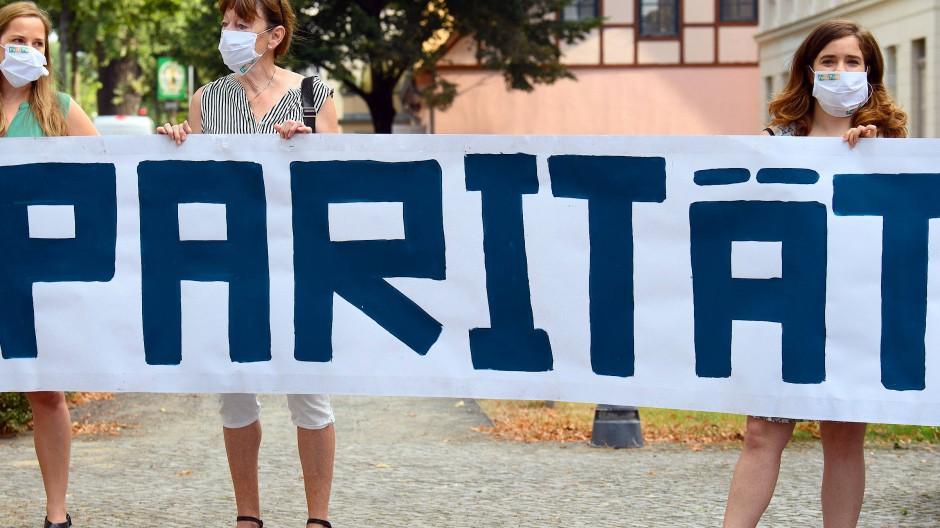 """Demonstranten des Frauenpolitischen Rates Land Brandenburg e.V. stehen am 20.8.2020 mit einem Transparent """"Parität"""" vor dem Justizzentrum in Potsdam."""