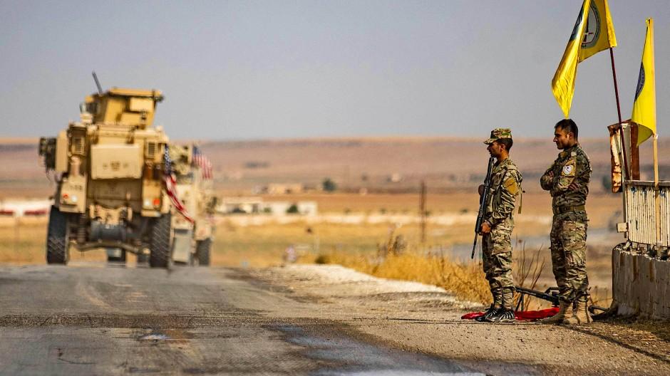 Ein amerikanisches Fahrzeug verlässt am Sonntag die Stadt Tal Tamr, beobachtet von kurdischen Milizionären.