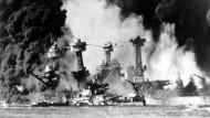 Ein Überraschungsangriff auf die amerikanische Pazifikflotte: Brennende Schlachtschiffe in Peral Harbour auf Hawaii. Am 7. Dezember 1941 begann mit dem Luftangriff der mit Deutschland verbündeten Japaner auf den Marinestützpunkt auch in Ostasien der Zweite Weltkrieg.
