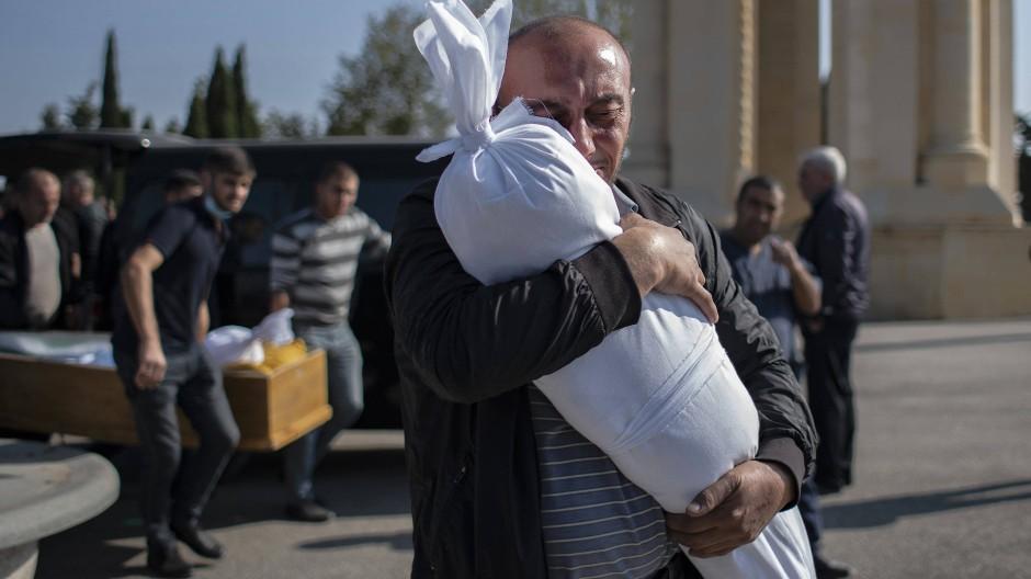 Opfer des Kriegs: Ein aserbaidschanisch-türkischer Vater umarmt am Samstag die sterblichen Überreste seiner zehn Monate alten Tochter  in Ganka.