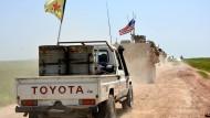 Ein Konvoi kurdischer YPG-Kämpfer und amerikanischer Soldaten patrouilliert entlang der türkisch-syrischen Grenze (Archivbild)