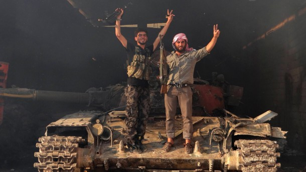 "Two members of the Free Syrian Army stand on a tank as they gesture ""V"" for victory in the Saraqib area near the northern city of Idlib"