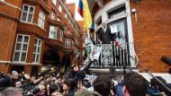 """Da war die Aussicht noch besser: Julian Assange zeigt vom Balkon der ecuadorianischen Botschaft den UN-Bericht, der seine """"willkürliche Inhaftierung"""" anprangert."""