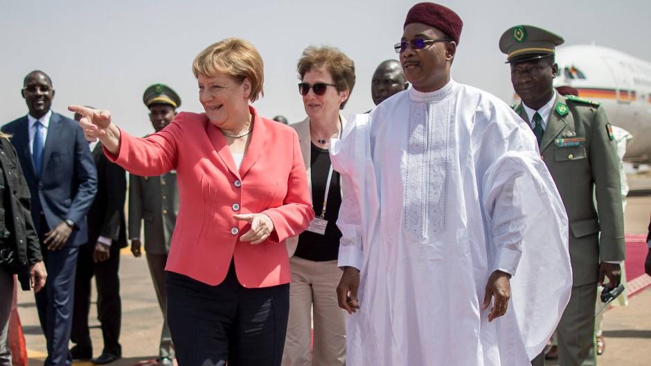 Der nigrische Präsident Mahamadou Issoufou (rechts, im weißen Gewand) begrüßt Bundeskanzlerin Angela Merkel.