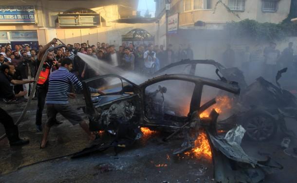 In Gaza: Palästinenser versuchen das Wrack zu löschen, in dem der Hamas-Kommandant durch israelische Raketen getötet wurde.